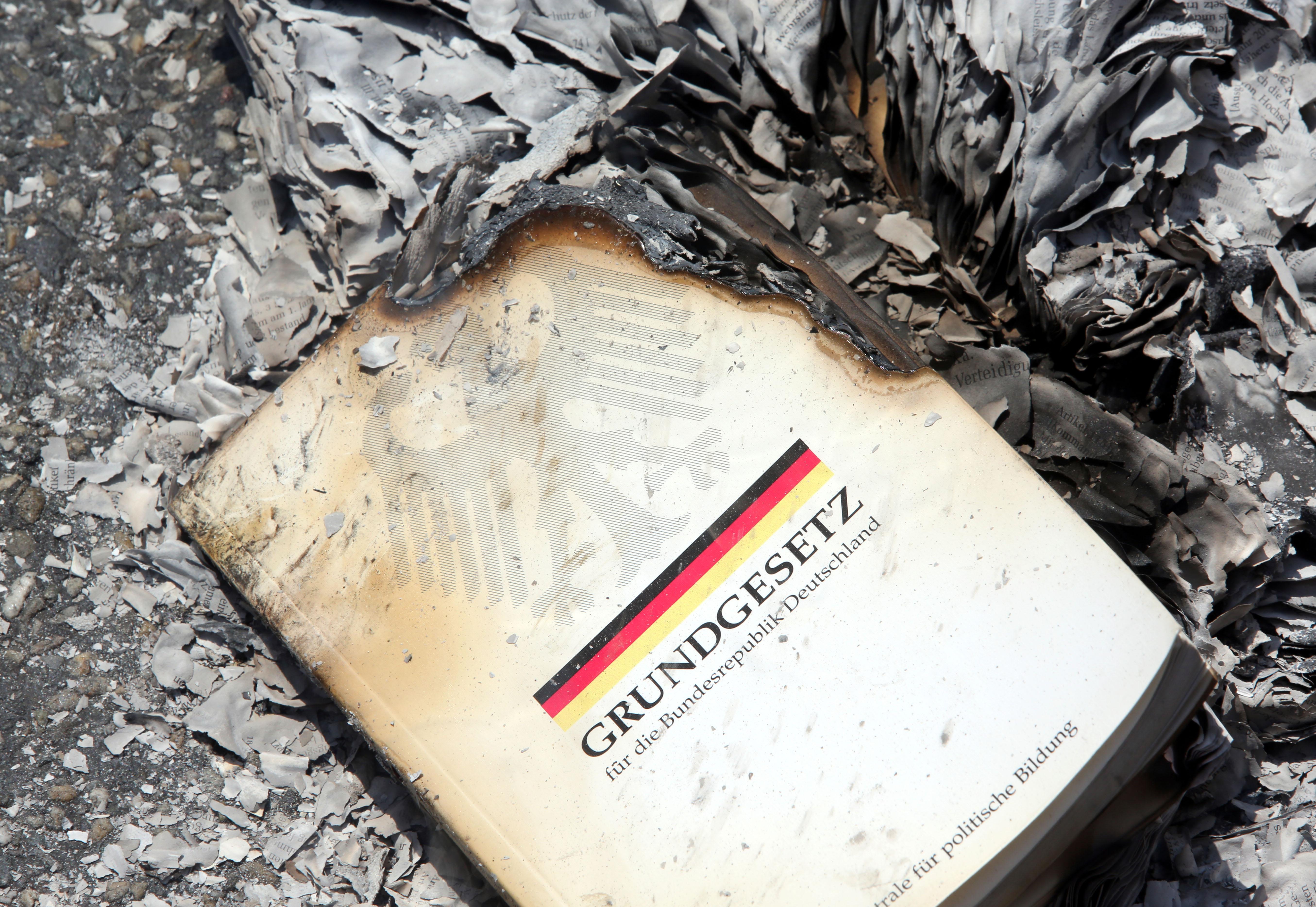 Demonstranten verbrennen am 08.06.2013 in Frankfurt am Main (Hessen) symbolisch ein Grundgesetz, um gegen die Polizeiaktionen gegen die kapitalismus-kritische Occupy-Bewegung vor einer Woche zu demonstrieren. Sie laufen dabei auf der selben Route, auf der am 1. Juni fast 1000 Menschen von der Polizei aufgehalten und stundenlang eingekesselt worden waren Foto: Frank Rumpenhorst/dpa